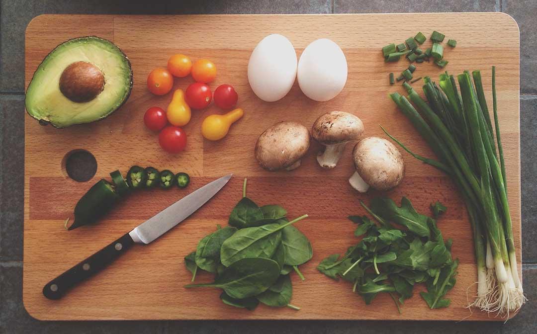 Eine Avocado, Tomaten, Peperoni, Eier, Pilze, Frühlingszwiebel, Spinat und Rucola liegen zusammen mit einem Messer auf einem Brett